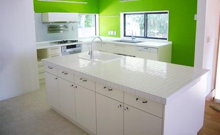白いアイランドキッチンとカラフルな壁紙